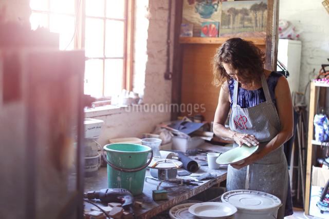 Female potter checking glazed ceramic plate in workshopの写真素材 [FYI03620068]