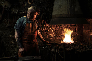 Mature male blacksmith heating metal on open fire in workshopの写真素材 [FYI03620075]