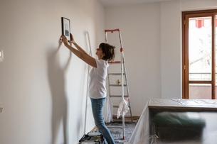 Senior woman putting picture frame on house interior white wallの写真素材 [FYI03620134]