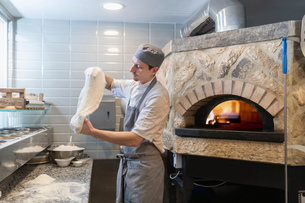 Chef tossing and stretching the dough for Pinsa Romana, a Roman style pizza blend reducing sugar andの写真素材 [FYI03620136]