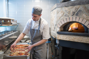 Chef putting tomato sauce onto Pinsa Romana, a Roman style pizza blend reducing sugar and saturatedの写真素材 [FYI03620140]