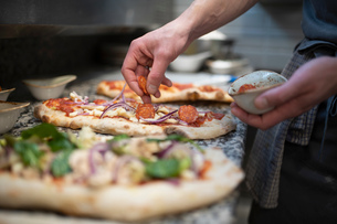 Chef placing sausage onto Pinsa Romana base, a Roman style pizza blend reducing sugar and saturatedの写真素材 [FYI03620143]