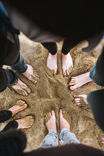 Male and female young adults standing barefoot in sand, cropped overhead viewの写真素材 [FYI03620257]