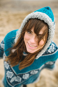 Woman in hooded top on beach, high angle portrait,  Barcelona, Spainの写真素材 [FYI03620263]