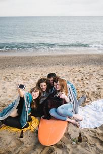 Friends taking selfie on surfboard at beach party, Barcelona, Spainの写真素材 [FYI03620271]