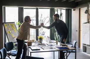 Businessmen holding hands in agreement in officeの写真素材 [FYI03620287]