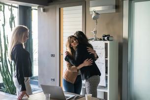 Businesswoman watching colleagues hugging in officeの写真素材 [FYI03620302]