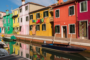 Moored boats on canal lined with pink, red, orange, yellow and green stucco houses decorated with cuの写真素材 [FYI03620354]