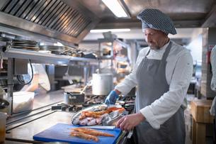 Chef preparing seafood dish in Italian restaurant kitchenの写真素材 [FYI03620361]