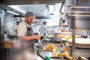Chef reading order in Italian restaurant kitchenの写真素材 [FYI03620369]