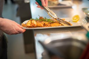Chef putting last touches to seafood dish in Italian restaurant kitchenの写真素材 [FYI03620374]