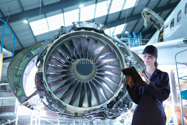 Composite image of female worker with digital tablet in aircraft maintenance factoryの写真素材 [FYI03620383]