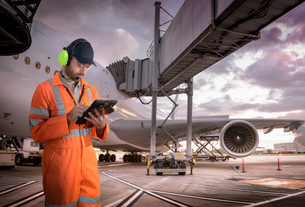 Composite image of airport worker using digital tablet with aircraftの写真素材 [FYI03620388]