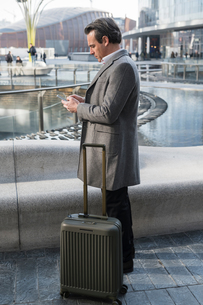 Businessman using smartphone in city centre, Milan, Lombardia, Italyの写真素材 [FYI03620422]