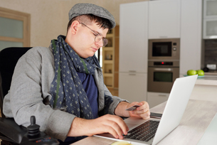 Physically impaired man making online purchase on laptop at homeの写真素材 [FYI03620473]