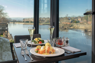 View of river with table setting at Italian restaurantの写真素材 [FYI03620592]