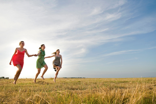 Girlfriends skipping on field, Eastbourne, East Sussex, United Kingdomの写真素材 [FYI03620781]