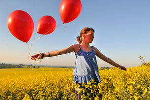 Girl with red balloons on rapeseed field, Eastbourne, East Sussex, United Kingdomの写真素材 [FYI03620786]