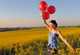 Girl with red balloons on rapeseed field, Eastbourne, East Sussex, United Kingdomの写真素材 [FYI03620788]