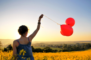 Girl with red balloons on rapeseed field, Eastbourne, East Sussex, United Kingdomの写真素材 [FYI03620789]