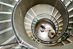 Businessman and businesswoman shaking hands below spiral staircaseの写真素材 [FYI03620790]