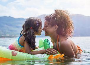 Mother rubbing noses with daughter on inflatable frog in lakeの写真素材 [FYI03620865]