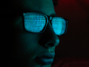 Cyber Crime, reflection in spectacles of virus hacking a computer, close up of faceの写真素材 [FYI03620870]