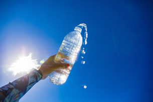 Woman holding water bottle against sunの写真素材 [FYI03620954]