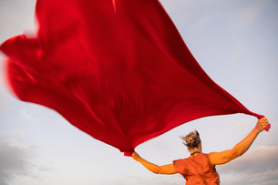 Woman holding up red cloth fluttering in windの写真素材 [FYI03620998]