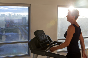 Woman walking on treadmill in gym facing city view, Manila, Philippinesの写真素材 [FYI03621006]