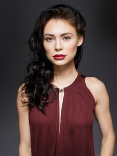 Beautiful young woman with long black hair, studio portraitの写真素材 [FYI03621044]