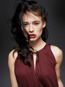Beautiful young woman with long black flyaway hair, studio portraitの写真素材 [FYI03621045]