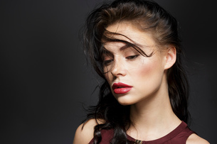 Beautiful young woman with long black flyaway hair, studio portraitの写真素材 [FYI03621047]