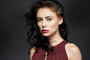 Beautiful young woman with long black hair, studio portraitの写真素材 [FYI03621049]