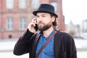 Man in trilby making smartphone call on city streetの写真素材 [FYI03621078]