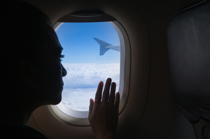 Woman travelling in airplane, looking out windowの写真素材 [FYI03621265]