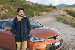 Man resting against car on roadside, enjoying view on hilltop, Villasimius, Sardegna, Italyの写真素材 [FYI03621267]