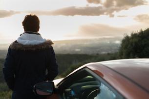 Man resting against car on roadside, enjoying view on hilltopの写真素材 [FYI03621268]