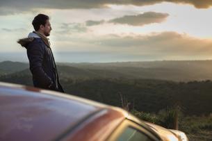 Man resting against car on roadside, enjoying view on hilltopの写真素材 [FYI03621275]