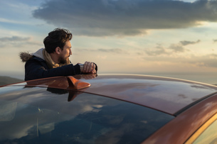 Man resting against car on roadside, enjoying view on hilltopの写真素材 [FYI03621277]