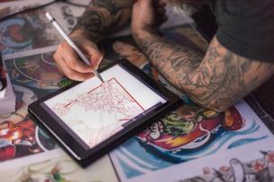 Tattooist sketching tattoo design on digital tabletの写真素材 [FYI03621278]