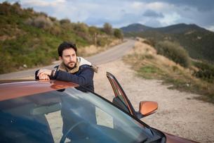 Man resting against car on roadside, enjoying view on hilltop, Villasimius, Sardegna, Italyの写真素材 [FYI03621281]