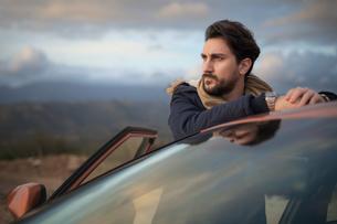 Man resting against car on roadside, enjoying view on hilltopの写真素材 [FYI03621285]