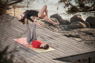 Women practising acro yoga at seasideの写真素材 [FYI03621289]