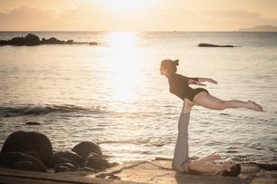 Women practising acro yoga at seasideの写真素材 [FYI03621290]