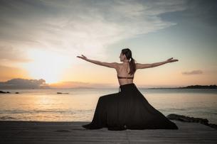 Woman practising yoga at seasideの写真素材 [FYI03621295]