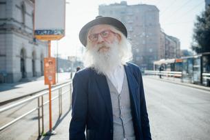 Senior businessman waiting at bus stop, Milano, Lombardia, Italyの写真素材 [FYI03621298]