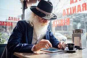 Senior businessman using digital tablet in cafe, Milano, Lombardia, Italyの写真素材 [FYI03621300]