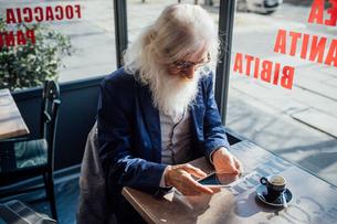 Senior businessman using digital tablet in cafe, Milano, Lombardia, Italyの写真素材 [FYI03621312]