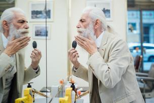 Senior businessman brushing beard in salonの写真素材 [FYI03621323]